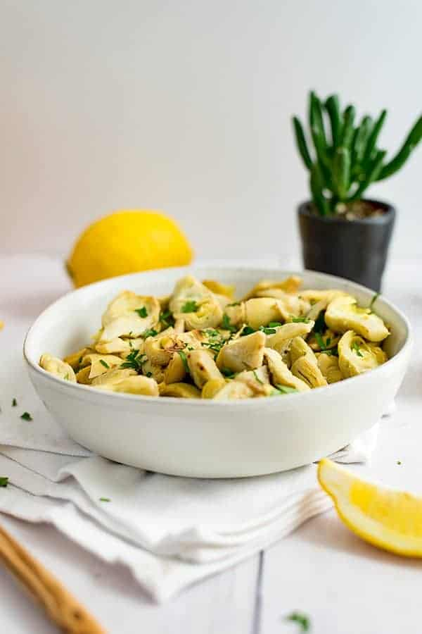 White bowl filled with lemon artichoke recipe. succulent plant in background