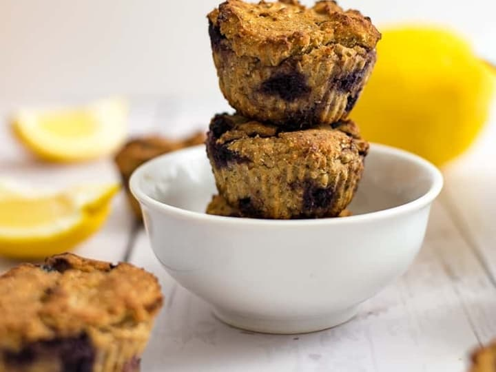 Two lemon blueberry muffins in a white bowl with a lemon in the background