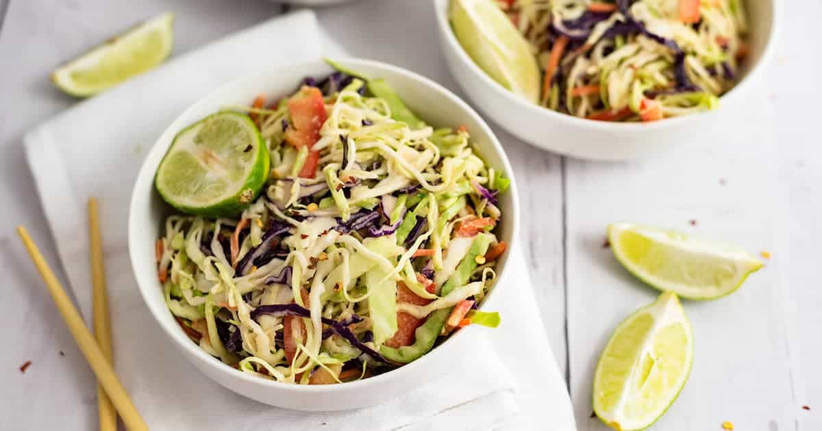 White bowl of spicy creamy asian slaw on a white napkin with chop sticks on the left side