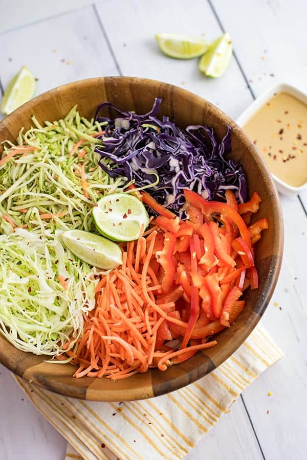 Large wooden bowl of veggies before tossing to make the spicy creamy asian slaw recipe