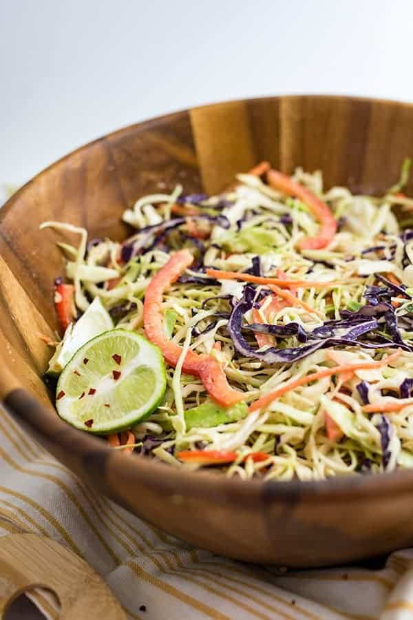 Large wooden salad bowl filled with spicy creamy asian slaw