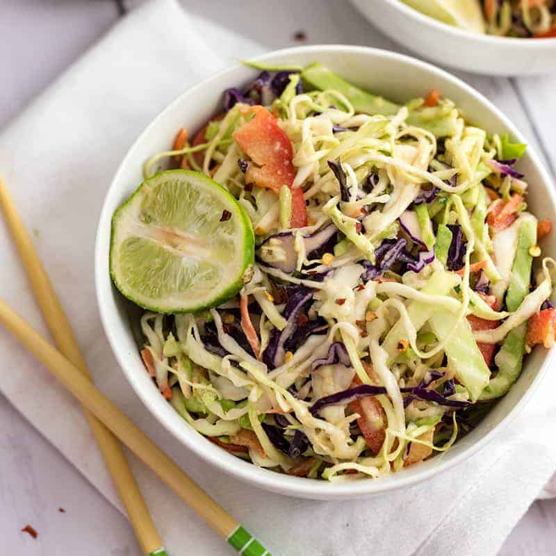 White bowl of spicy creamy asian slaw with a lime in the bowl, with chop sticks on the left side