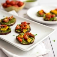 Sweet potato pizza bites on a white plate with a bowl of tomatoes in the background.