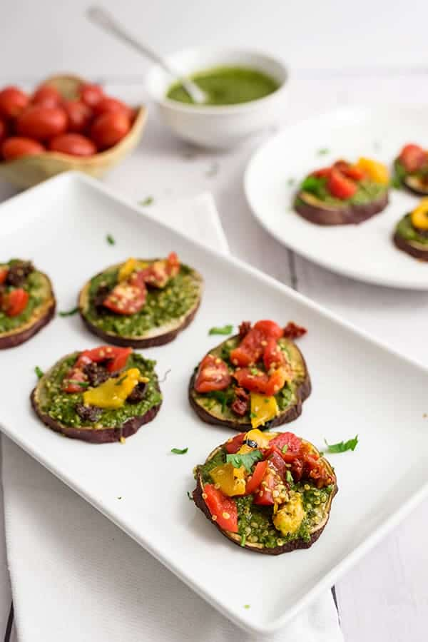 Sweet potato pizza bites on a white rectangular plate with tomatoes and pesto in the background.