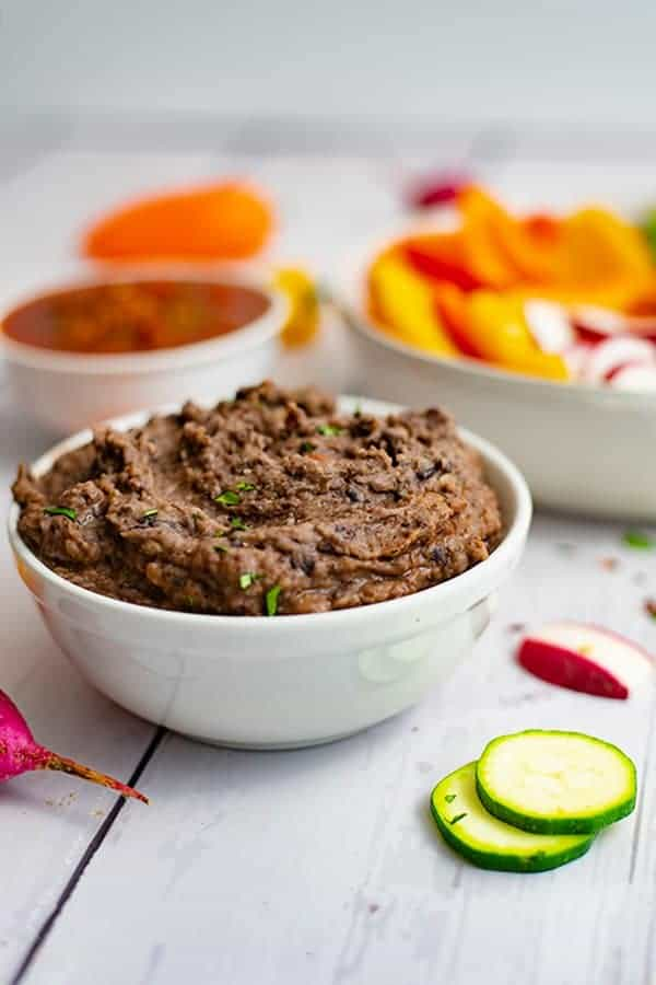 White bowl full of 3 ingredient black bean dip recipe with sliced veggies in the background