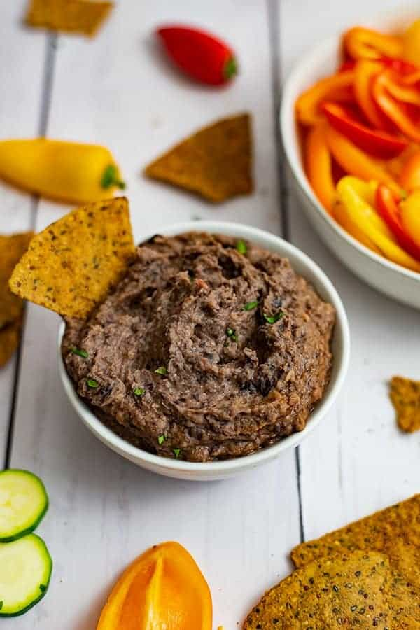 Bowl of the 3 ingredient black bean dip recipe with a chip in the dip with veggies in the background