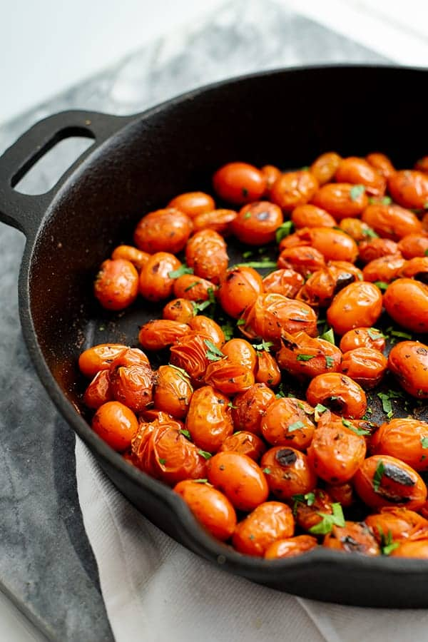 Cast iron skillet with blistered tomatoes over a white napkin