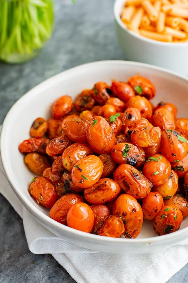 White bowl of blistered tomatoes over a white napkin with a small bowl of lentil pasta in the background