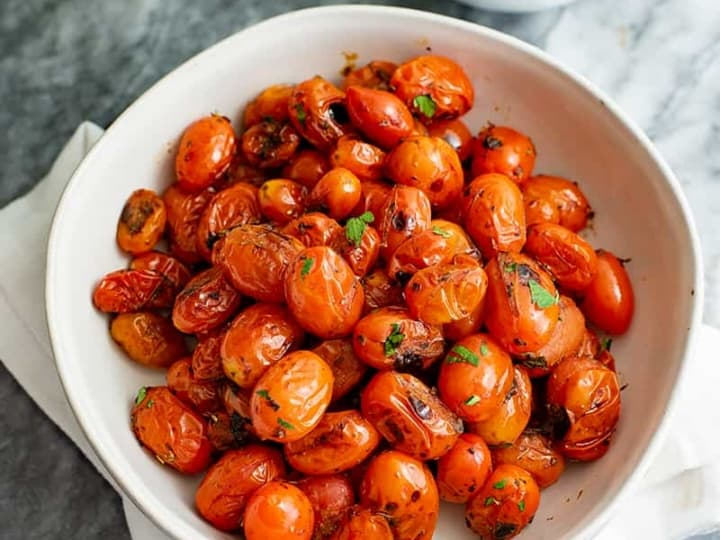 Overhead shot of a large white bowl of blistered tomatoes topped with parsley
