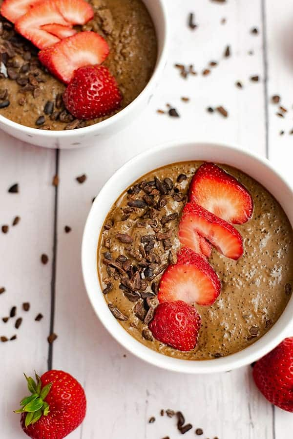 Breakfast quinoa bowl topped with sliced strawberries and surrounded by strawberries and cacao nibs.