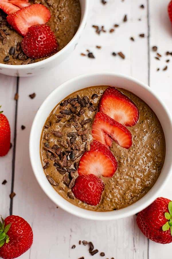 Overhead shot of a white bowl filled with breakfast quinoa bowl recipe, with second bowl in the background and surrounded by strawberries and cacao nibs.