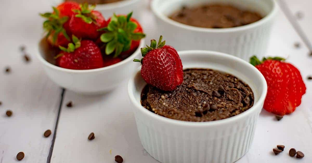 Two single serve brownies in white ramekins surrounded by strawberries