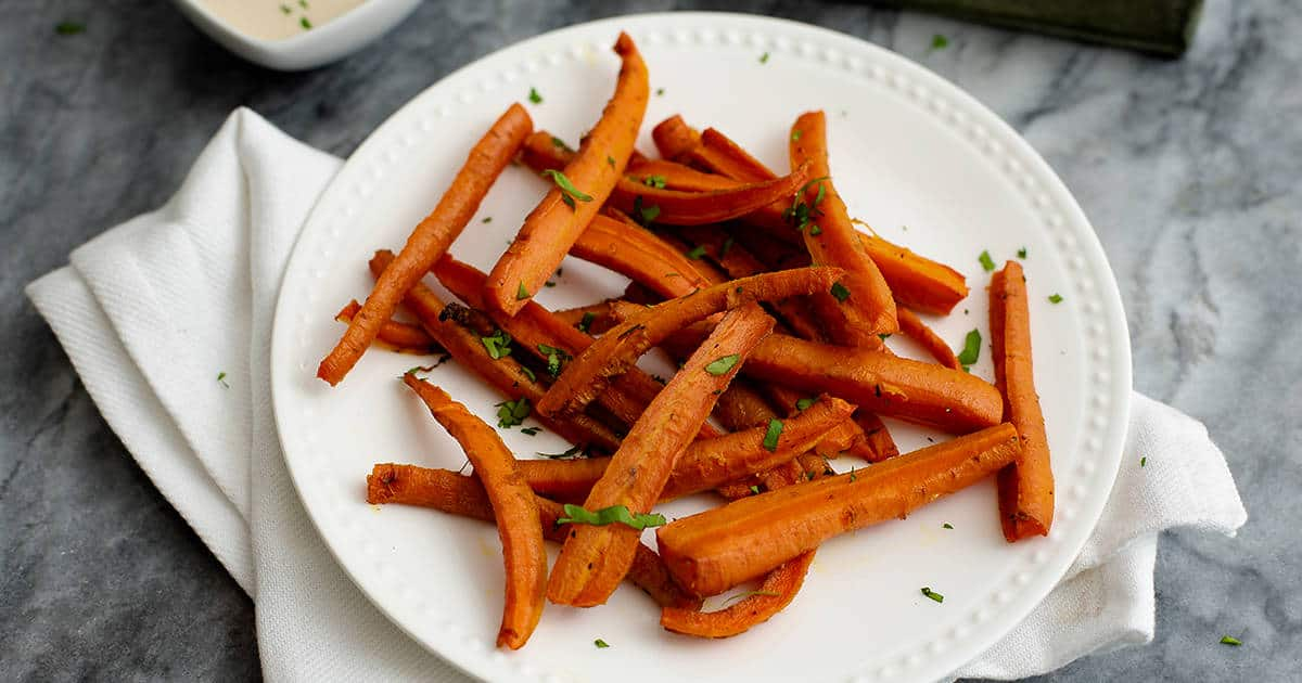 Spicy Curry Oven Baked Carrot Fries on a white plate on a white napkin