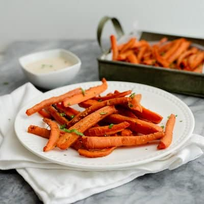 spicy curry oven baked carrot fries on a white plate and a white napkin with a small ramekin of lime cilantro tahini sauce in the background