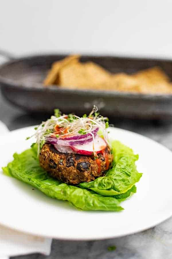 Vegan Black bean burger recipe over lettuce leaves topped with sliced radish, red onion and sprouts on a white plate with chips in the background