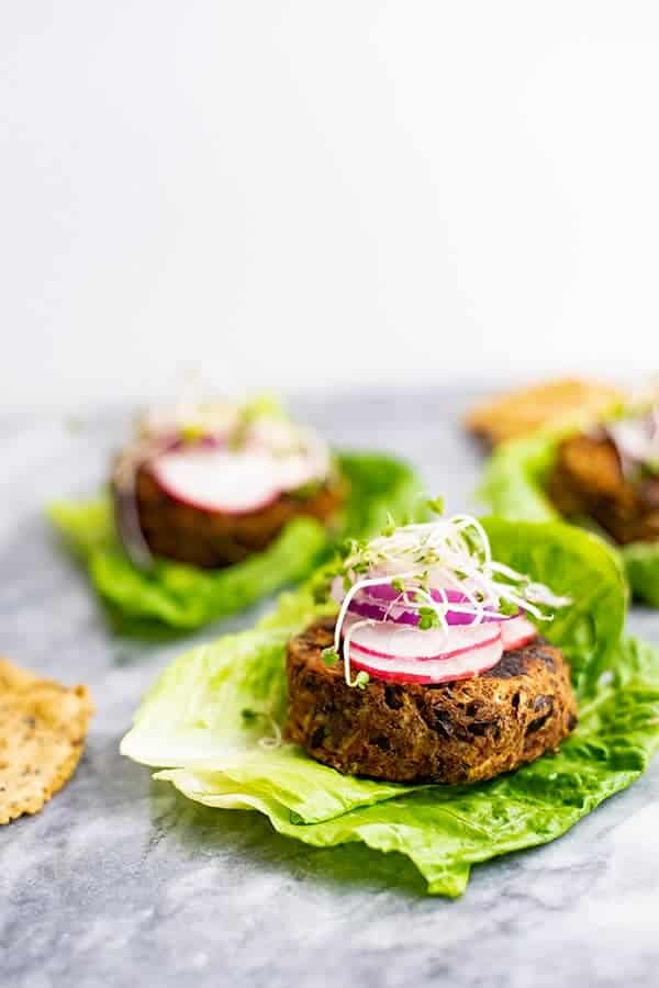 Vegan Black bean burger recipe over lettuce leaves topped with sliced radish, red onion and sprouts.