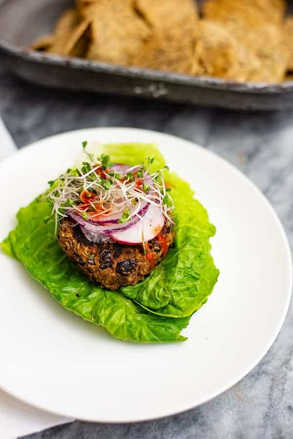 Overhead shot of vegan Black bean burger recipe over lettuce leaves topped with sliced radish, red onion and sprouts on a white plate with chips in the background