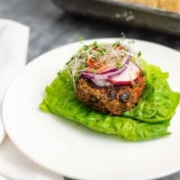 Vegan Black bean burger recipe over lettuce leaves topped with sliced radish, red onion and sprouts on a white plate.