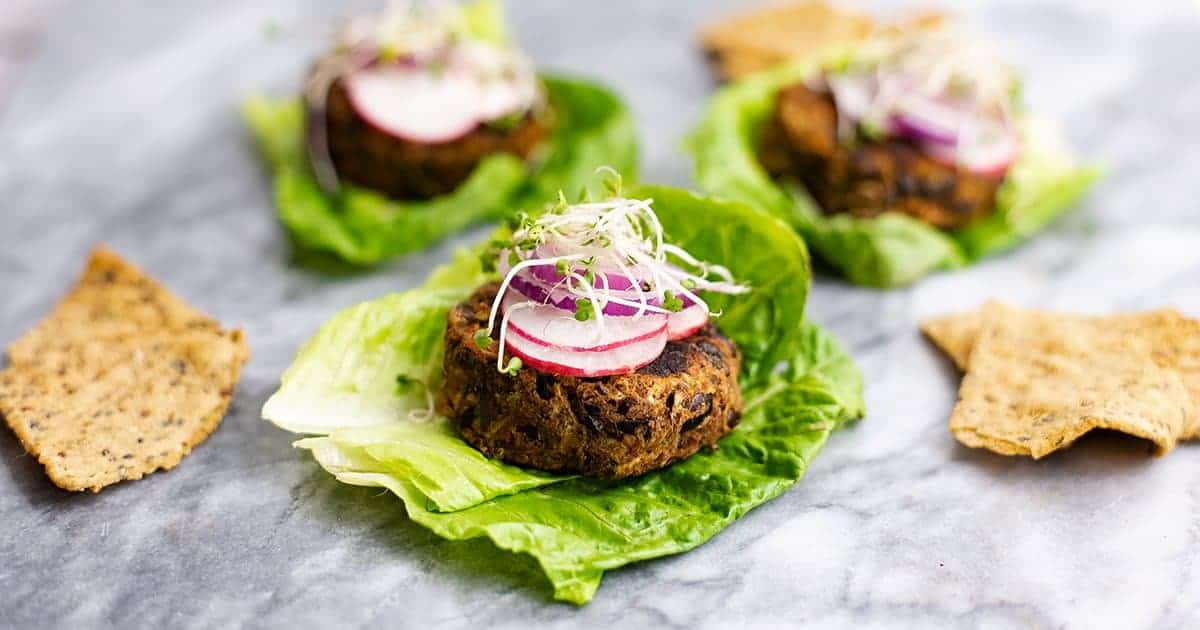 Vegan Black bean burger recipe over lettuce leaves topped with sliced radish, red onion and sprouts on a marble slab with burgers in the background.