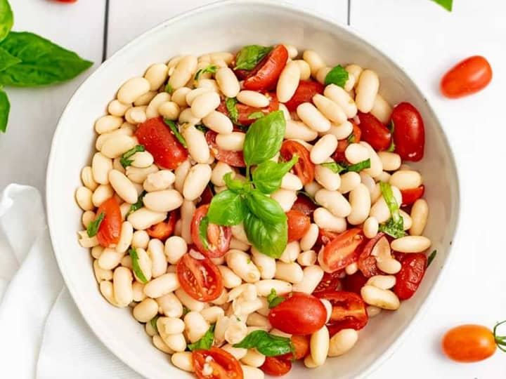 Overhead shot of bowl of vegan cannellini bean salad in a white bowl with tomatoes and basil around the plate.