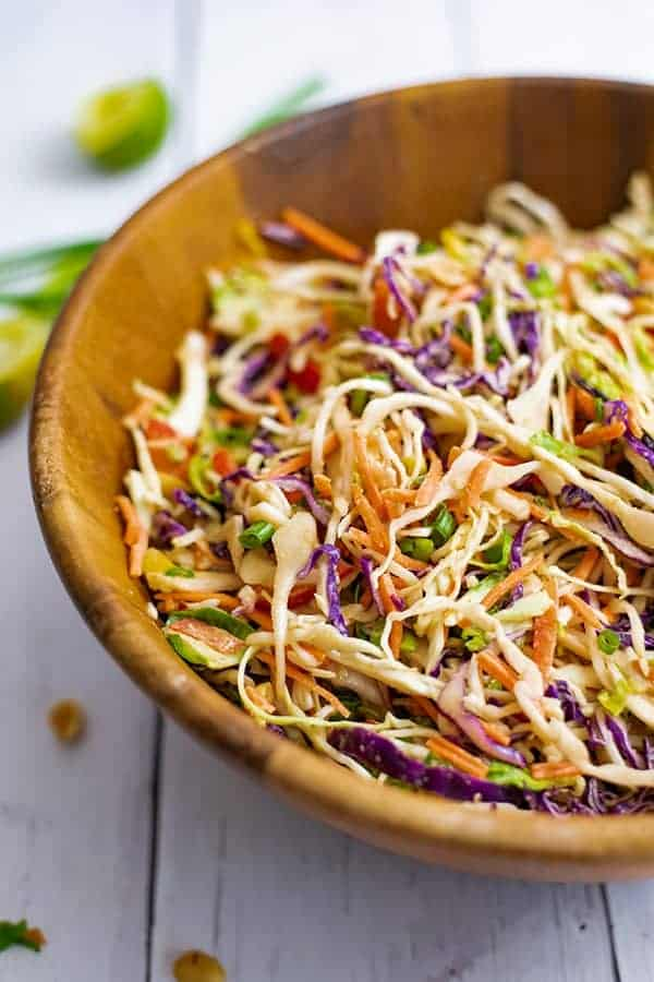Large wooden salad bowl filled with Asian Cabbage slaw surrounded by peanuts and limes.