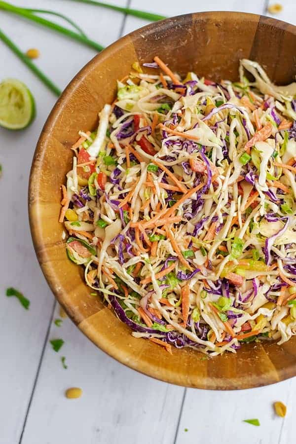 Large wooden salad bowl filled with Asian Cabbage Slaw