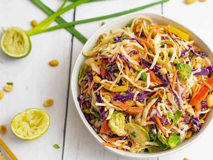 Overhead shot of bowl of Asian Cabbage Slaw with green onions and limes in the background.