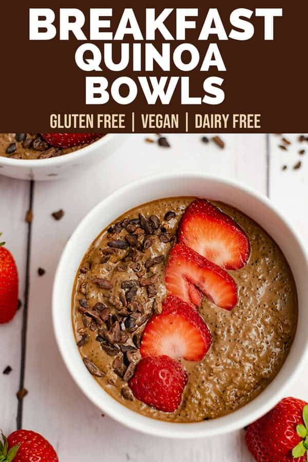 Breakfast quinoa bowl recipe in a white bowl surrounded by strawberries and cacao nibs.