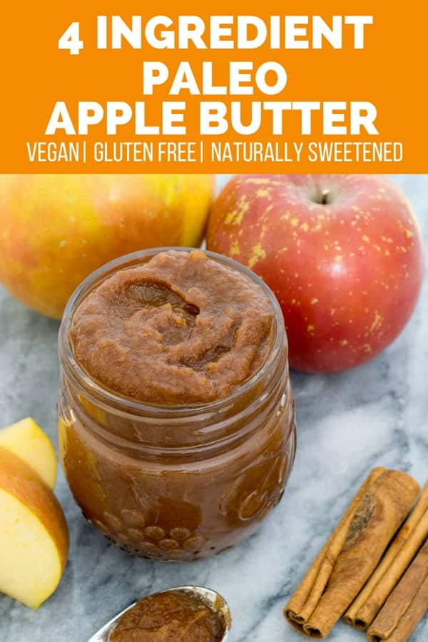 Glass mason jar filled with apple butter with cinnamon sticks and sliced apples surrounding the mason jar.