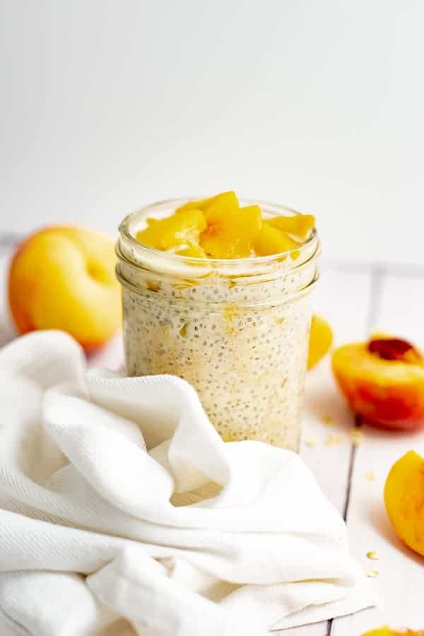 Small mason jar filled with peach overnight oats with yogurt with sliced peaches on top surrounded by a white napkin and sliced peaches