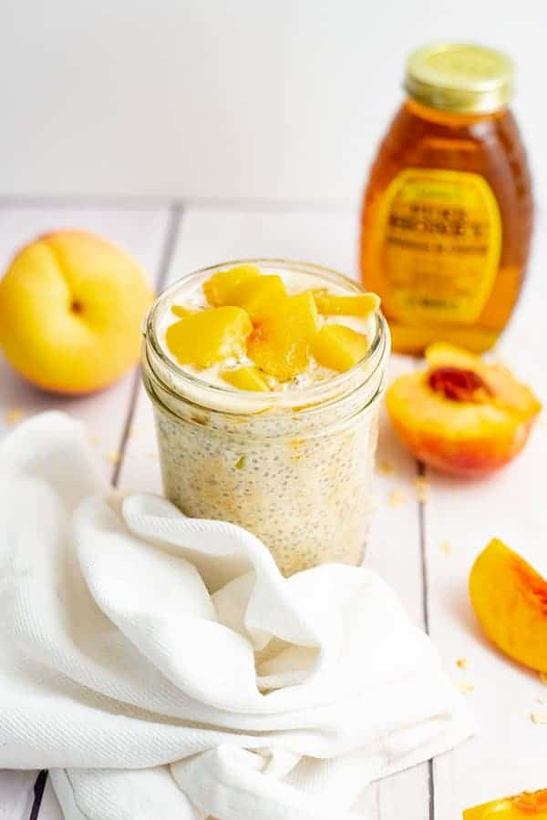Small mason jar filled with peach overnight oats with yogurt with sliced peaches on top surrounded by sliced peaches and a bottle of honey.