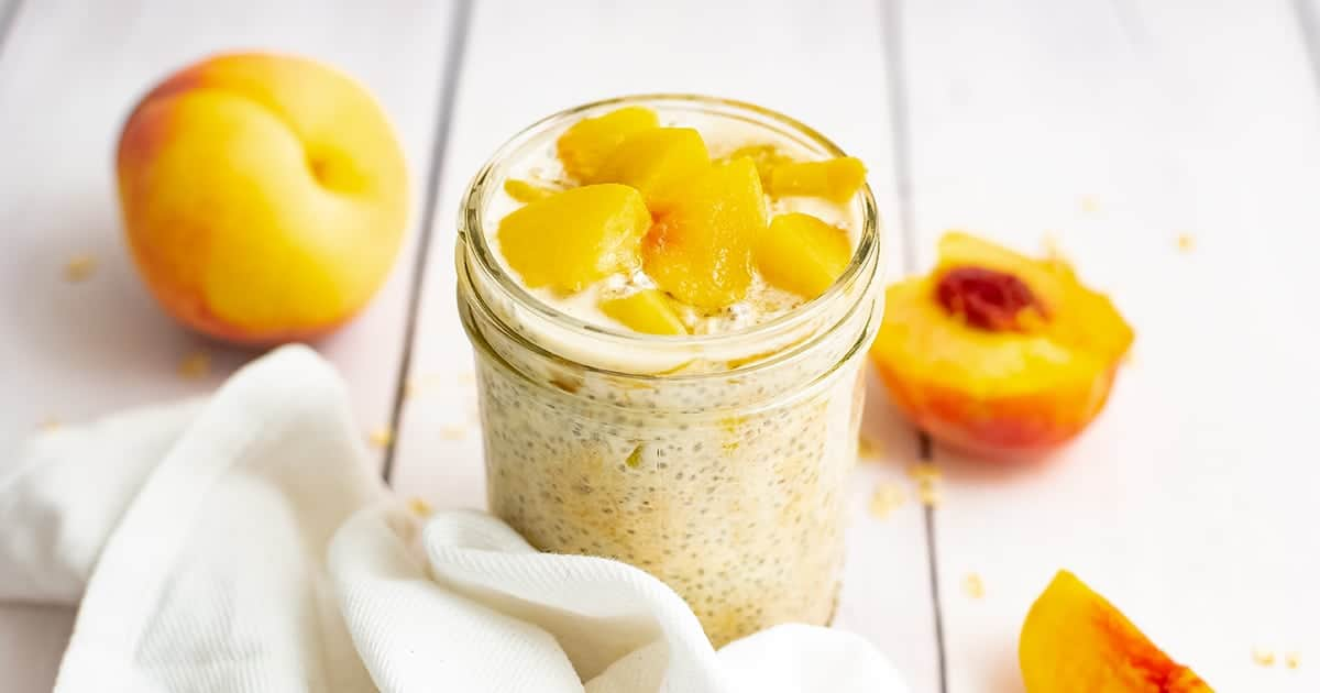 Small mason jar filled with peach overnight oats with yogurt with sliced peaches on top. Surrounded by a white napkin