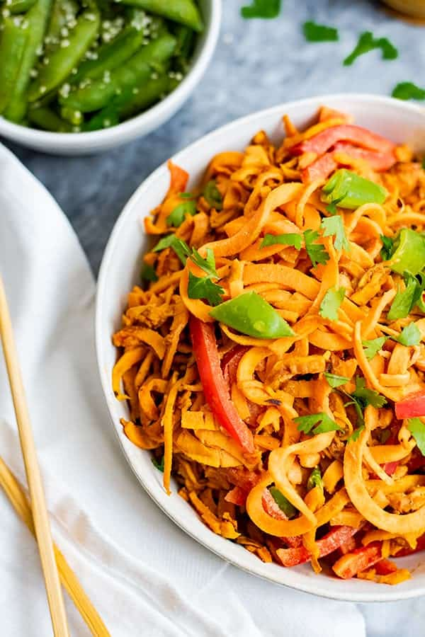 Overhead shot of spicy peanut spiralized sweet potatoes in a large white bowl with chopsticks to the left side and green snap peas in the background
