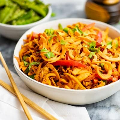 spicy peanut spiralized sweet potatoes in a large white bowl with chopsticks to the left side and green snap peas in the background