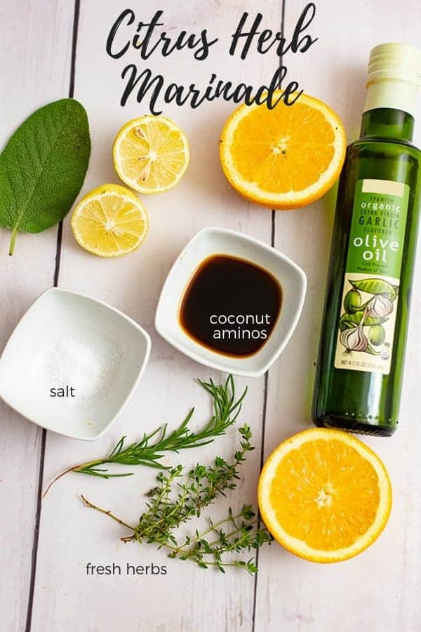 Ingredients for the Citrus Herb Marinade: sliced lemons and oranges, fresh herbs, salt, coconut aminos and a bottle of garlic olive oil
