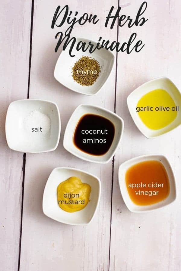Ingredients for the Dijon Herb Marinade in white ramekins: thyme, garlic olive oil. apple cider vinegar, dijon mustard, salt, coconut aminos