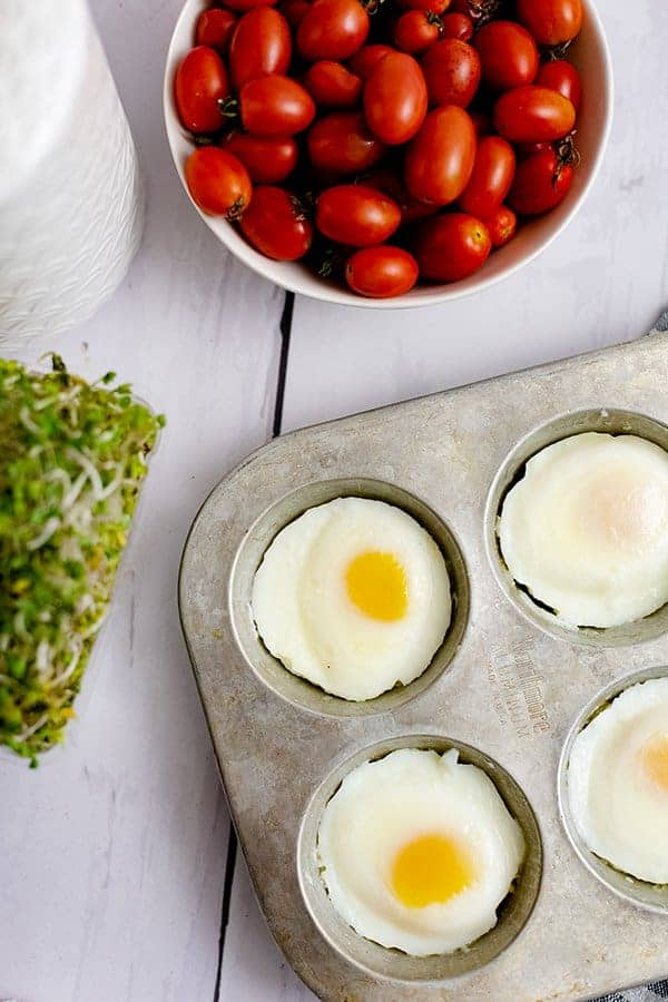 Overhead shot of a muffin tin filled with perfectly poached eggs in the oven with sprouts and tomatoes in the background