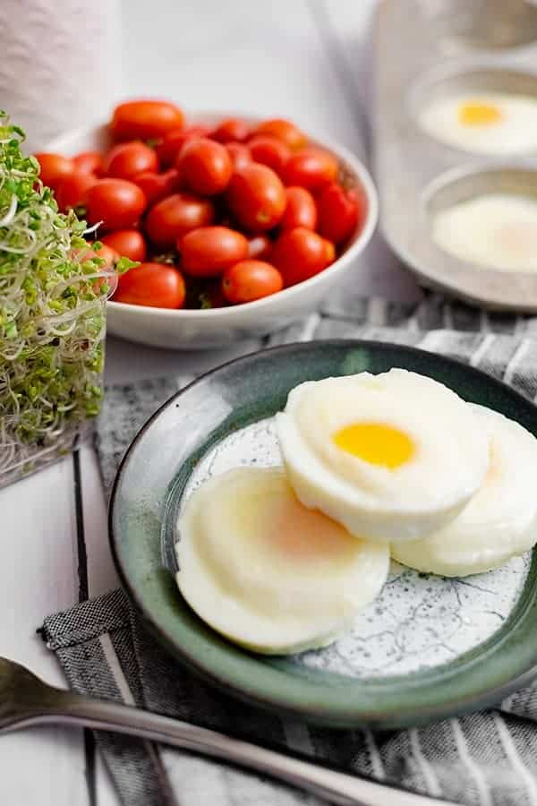 Three perfectly poached eggs in the oven on a blue plate over a blue striped napkin with a fork in front of the plate and a bowl of tomatoes and a muffin tin filled with poached eggs in the background
