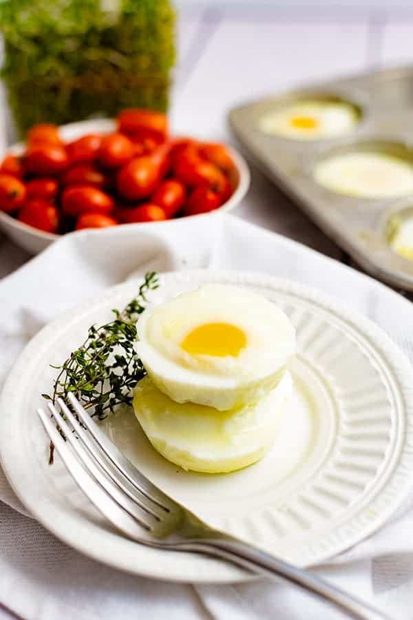 Two perfectly poached eggs in the oven on a white plate with a fork and springs of thyme on the plate with tomatoes and muffin tin in the background