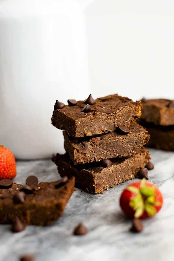 Three vegan black bean brownies with a strawberries and single brownies around them on a marble slab.