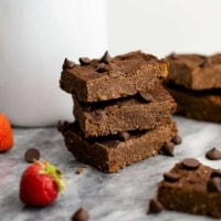 Close up shot of Three vegan black bean brownies with a strawberries and single brownies around them on a marble slab.