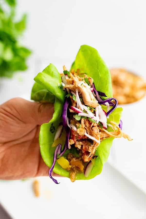 Whole30 slow cooker cajun chicken recipe shredded in a lettuce wrap with red cabbage and sliced radishes on top being held by hand like a taco .