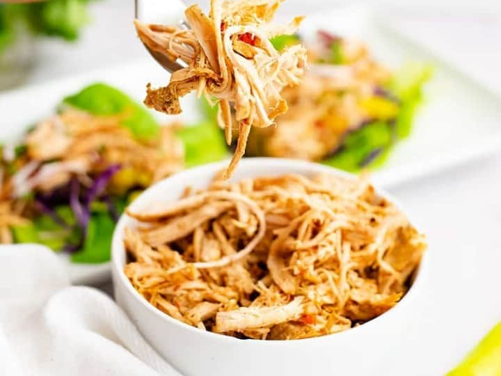 Whole30 slow cooker cajun chicken recipe shredded in a large white bowl with a fork filled with shredded jerk chicken above the bowl.