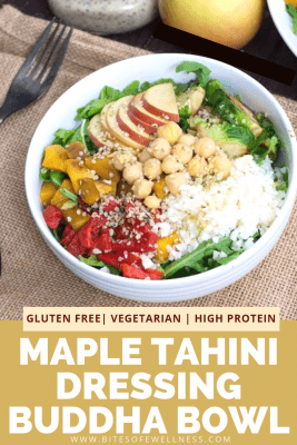 Fall Buddha Bowl with Maple Tahini Dressing in a white bowl over a brown napkin. Salad is filled with roasted veggies, apples, chickpeas and cheese