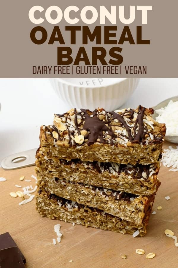 4 Vegan coconut oatmeal bars stacked on top of each other with coconut flakes and oats sprinkled around