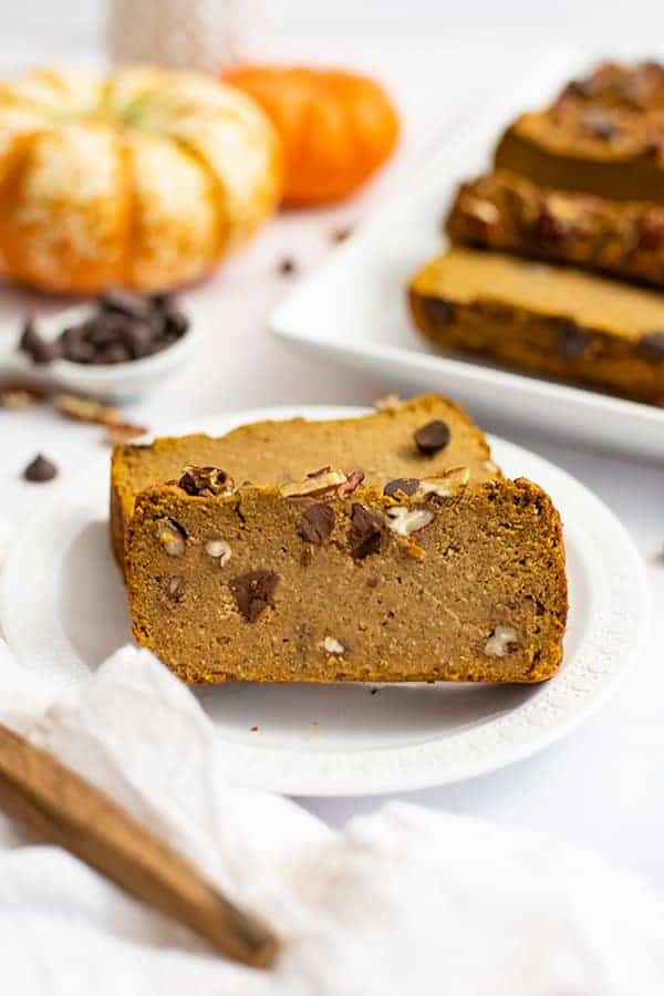 Two slices of healthy pumpkin bread recipe on a white plate with pumpkins in the background