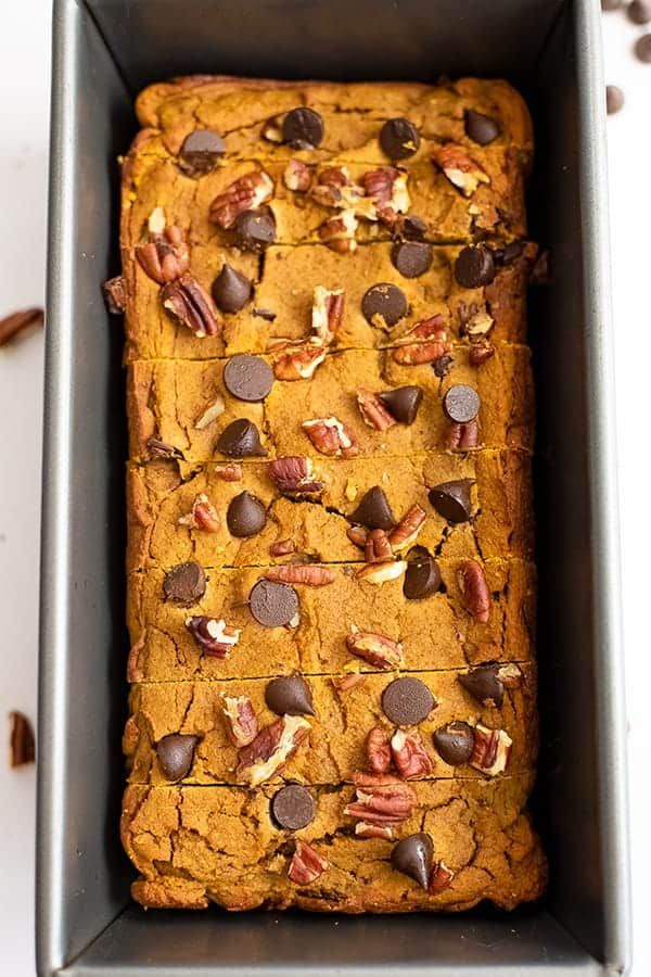 Loaf pan filled with healthy pumpkin bread recipe topped with chocolate chips and pecans