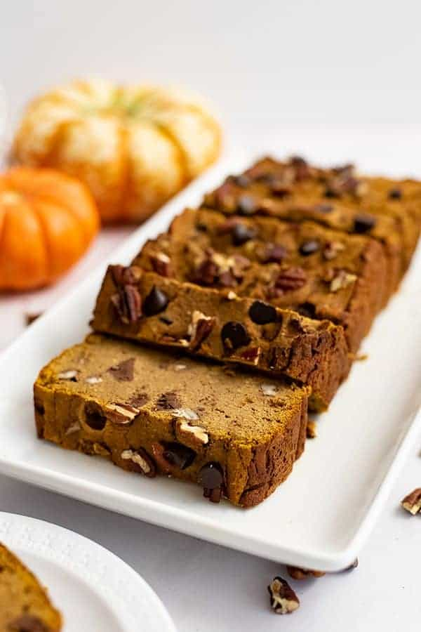 Healthy pumpkin bread recipe cut into slices over a white rectangular plate with pumpkins in the background