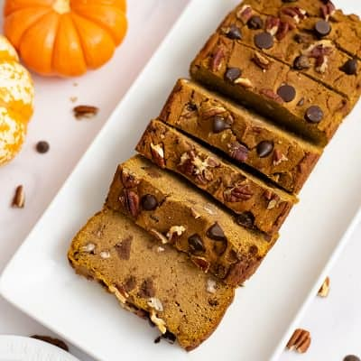 Overhead shot of healthy pumpkin bread recipe cut into slices over a white rectangular plate with pumpkins in the background