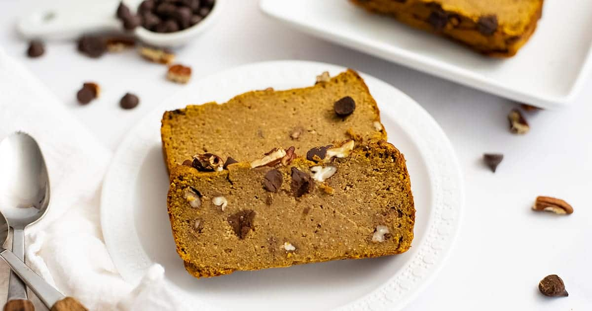 Two slices of healthy pumpkin bread recipe on a white plate with chocolate chips and pecans in the background